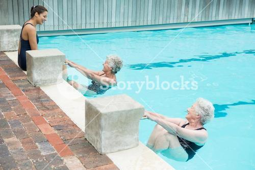 Trainer interacting with senior women at poolside