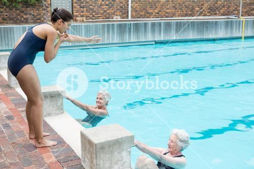 Swimming instructor assisting senior women