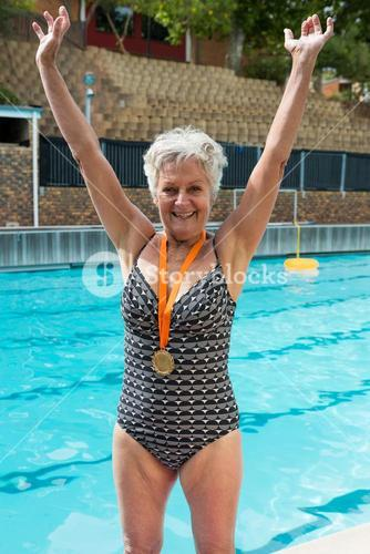 Excited senior woman with gold medals around her neck standing at poolside
