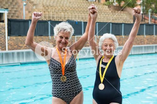 Excited senior women with gold medals standing at poolside