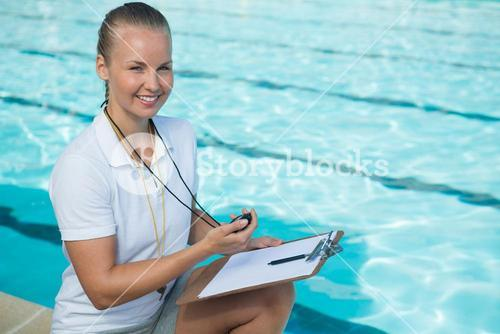 Smiling swim coach holding clipboard and stopwatch at poolside