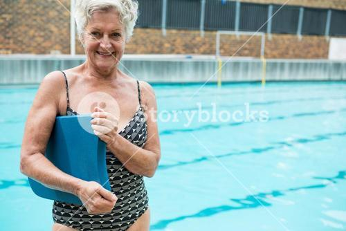 Smiling senior woman holding kickboard at poolside