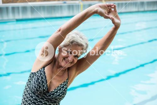 Smiling senior woman exercising at poolside