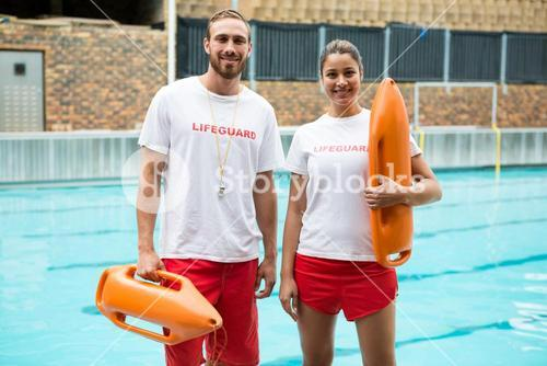 Two lifeguards standing with rescue buoy at poolside