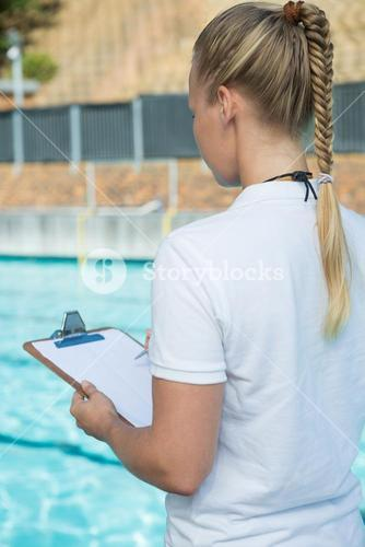 Female coach writing on clipboard at poolside