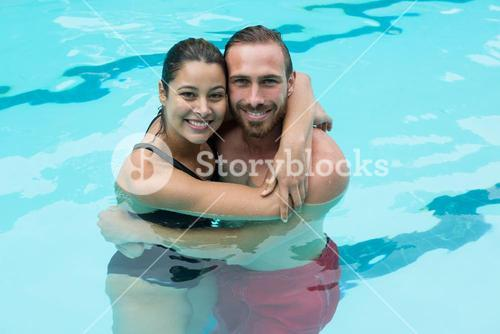 Smiling couple embracing in swimming pool