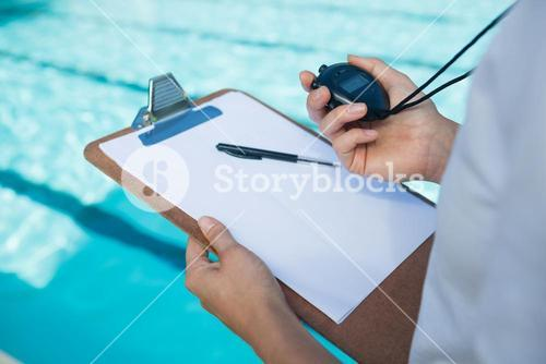 Swim coach looking at stopwatch at poolside