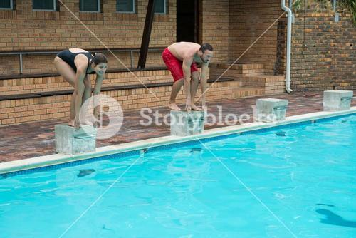 Couple preparing to dive in pool