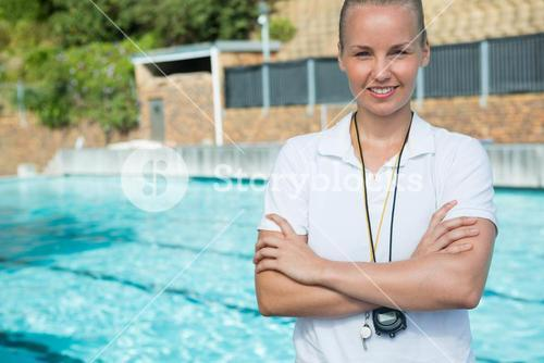 Female trainer standing with arms crossed at poolside