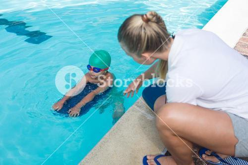 Female trainer training a boy for swimming
