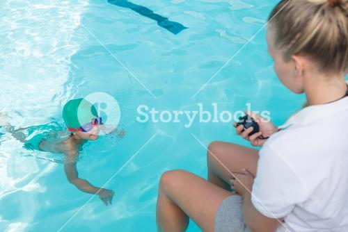Female trainer monitoring time of boy swimming in pool