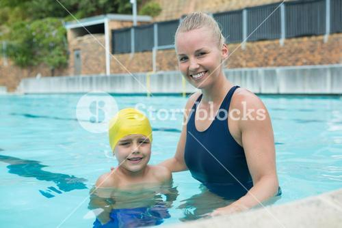 Portrait of female instructor and young boy standing in pool
