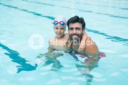 Portrait of father and young boy playing in pool