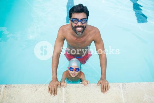 Portrait of father and son wearing swimming goggles in pool