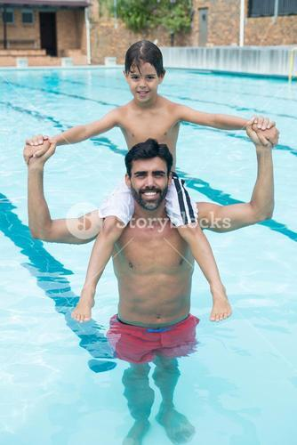 Father carrying son on shoulder in pool