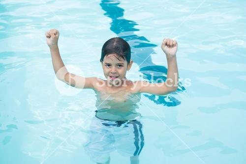 Young boy standing with arms up in pool