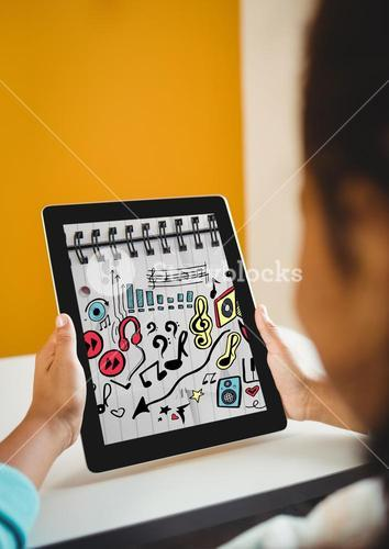 Kid at desk holding tablet showing music doodles on sketchbook