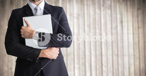Business man mid section holding device against blurry wood panel