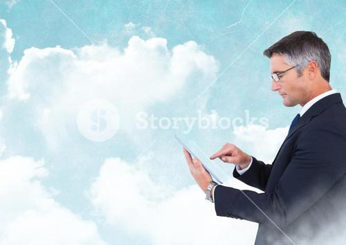 Businessman with tablet with blue cloudy sky