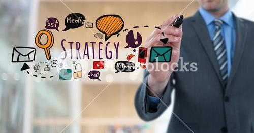 Businessman writing Strategy text with drawings graphics