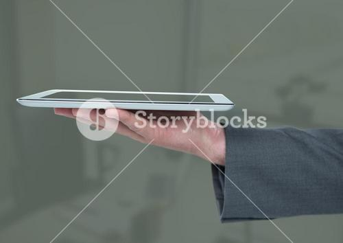 Hand holding tablet  against dim background