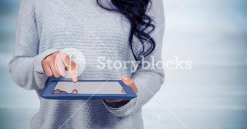 Woman mid section with tablet against blurry blue wood panel