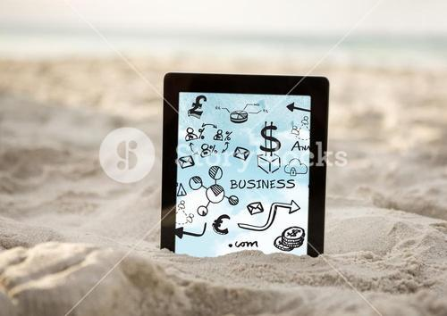 Tablet in sand showing black business doodles and sky