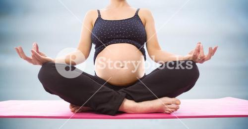 Pregnant woman meditating against blurry blue wood panel
