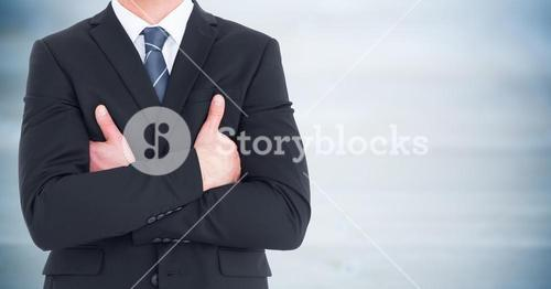 Business man mid section with arms crossed against blurry blue wood panel