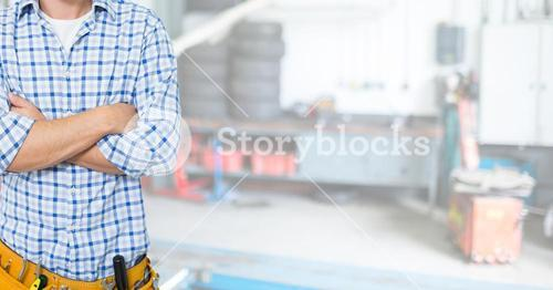 mechanic in his garage with his hands folded. Blurred background