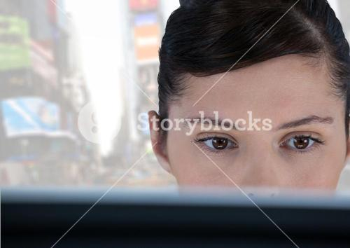 Woman on laptop with bright city background