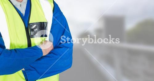 Builder with his hands folded on blurred background of the city