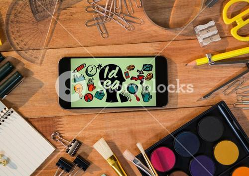 Phone on desk with art supplies showing head doodle against green background