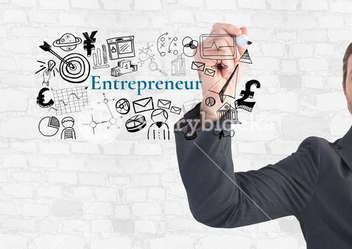 Businessman writing Entrepeneur text with drawings graphics