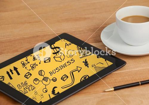 Tablet on table with coffee showing black business doodles and yellow background