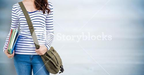 Woman with books and bag against blurry blue wood panel