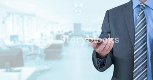 Businessman with phone in bright office