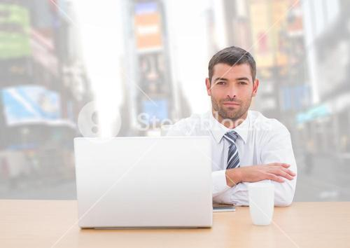 Man with laptop against bright city background
