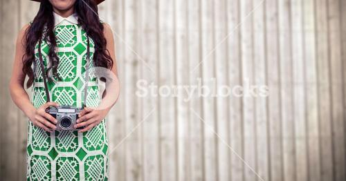 Woman with camera against blurry wood panel