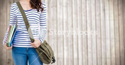 Woman with books and bag against blurry wood panel