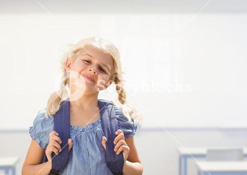 Young girl happy with bag in classroom