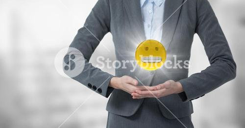 Mid section of business woman with emoji and flare between hands against blurry grey stairs