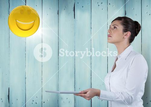 Business woman with tablet looking up at emoji and flare against blue wood panel