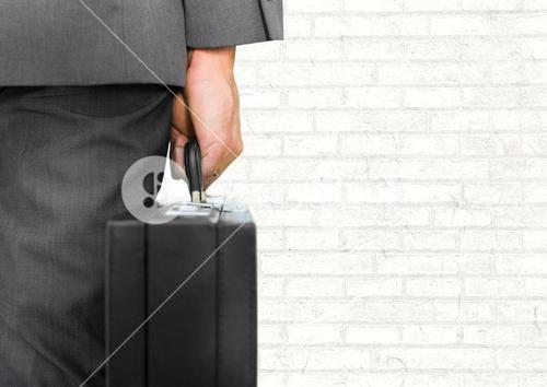 Businessman with briefcase facing white wall