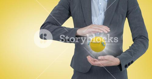 Business woman mid section with emoji between hands and flare against yellow background