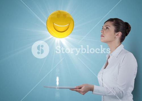 Business woman with tablet looking up at emoji and flare against blue background