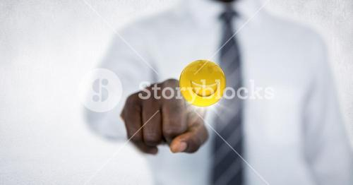 Business man mid section touching emoji with flare against white wall