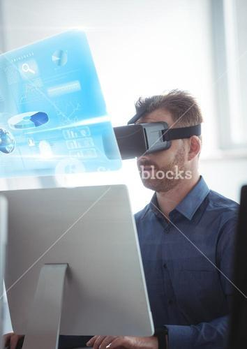 Man on computer wearing VR Virtual Reality Headset with Interface