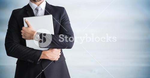 Business man mid section holding device against blurry blue wood panel
