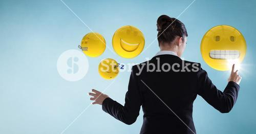 Back of business woman touching emojis against blue background